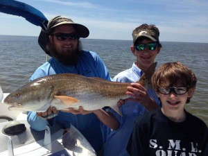 Blue Smith, center, caught this fine 26 inch redfish off Hardy Point while fishing with Dan and Andrew Deaver and Luke Cocke. They also scored trout, Spanish mackerel and flounder.