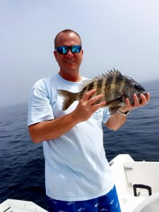 Alan Folsom from Valdosta with one of many sheepshead his family brought to the cleaning table.