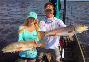 Chaeli Norwood and Luke Matthews with a pair of schooling redfish.