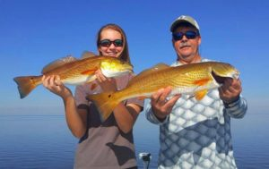 Jim and Morgan Carnes with a beautiful pair of schoolie redfish.